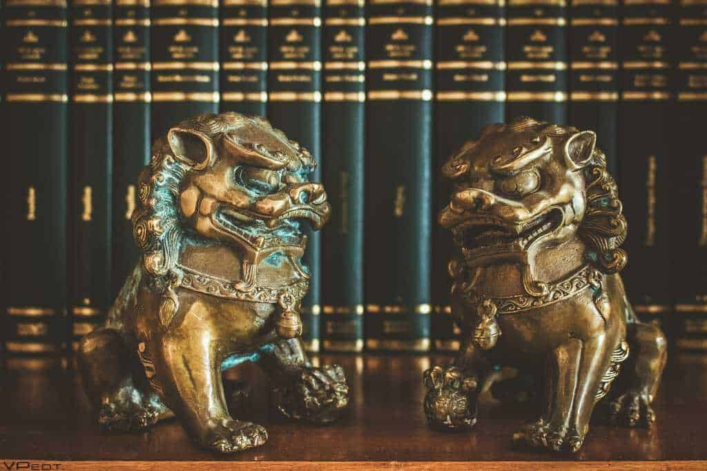 2 Chinese lions in front of books gold and black