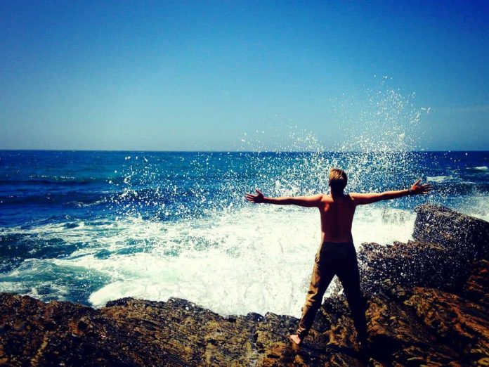 Man standing by ocean on rocks with arms in the air for success.